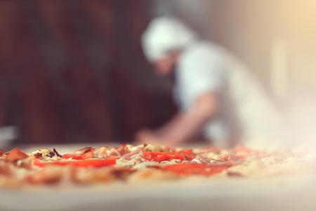 Close-up de pizza, chef derrière