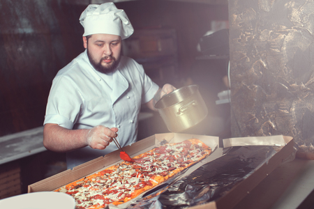 Close-up of pizza, chef behind