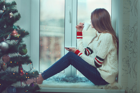 Young beautiful woman with reddish hair sitting home by the window with cup of hot coffee wearing knitted warm sweater.