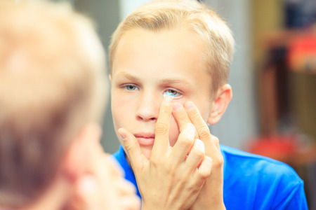 Shot of a young man trying to apply contact lenses in front of a mirror Stockfoto