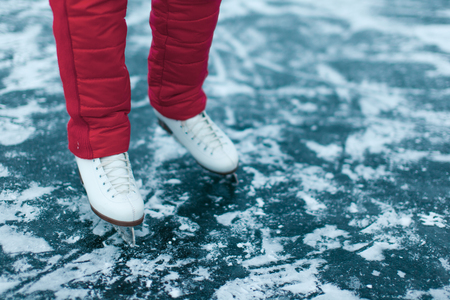 Woman ice skating. winter outdoors on ice rink. ice and legs