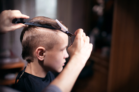 Beautiful young hairdresser giving a new haircut to male customer at parlor Stock Photo