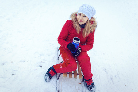 Happy young woman enjoying a winter sleigh ride on a winter slope Stock Photo