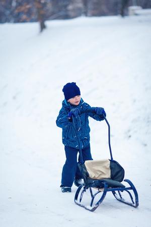 to go sledding: Winter fun boy up the hill to sledding