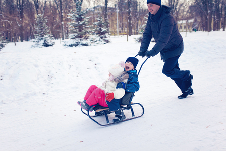 7 year old boys: Young Family Running Through Snow With Sled
