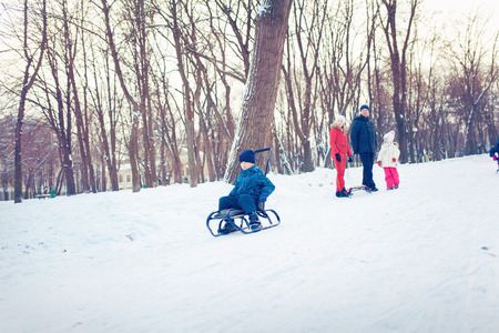 cold season: happy family with child on sled walking in winter outdoors