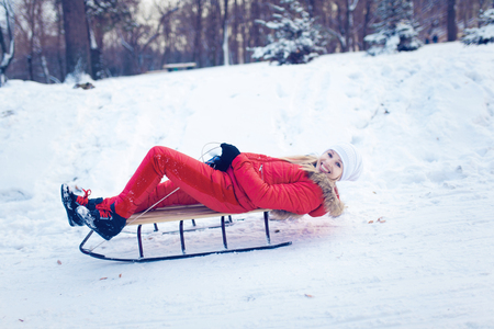 sledging people: Happy young woman enjoying a winter sleigh ride on a winter slope Stock Photo