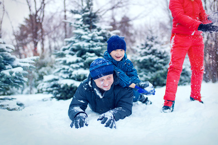 happy young family spending time outdoor in winter (focus on the father) Stock Photo