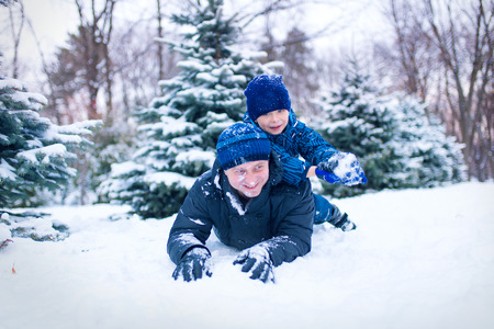 7 year old boys: happy young family spending time outdoor in winter (focus on the father) Stock Photo