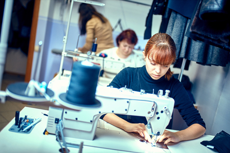 seamstress sews clothes. Workplace of tailor - sewing machine, rolls of thread, fabric, scissors. Stok Fotoğraf