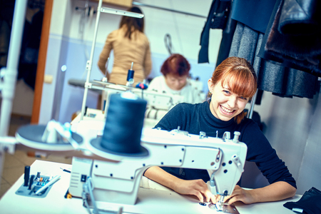 seamstress sews clothes. Workplace of tailor - sewing machine, rolls of thread, fabric, scissors. 스톡 콘텐츠
