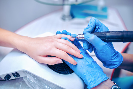 Manicurist removing cuticle from the girl client nail at beauty salon. Stock Photo