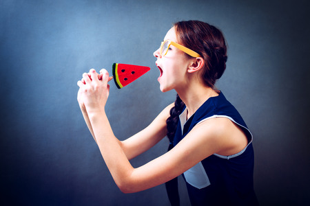Funny girl eating lollipop on a blue background, studio Stock Photo