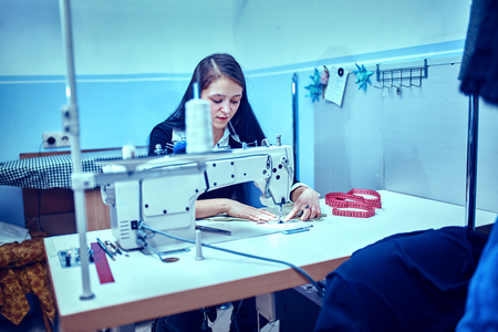 seamstress sews clothes. Workplace of tailor - sewing machine, rolls of thread, fabric, scissors. Stock Photo