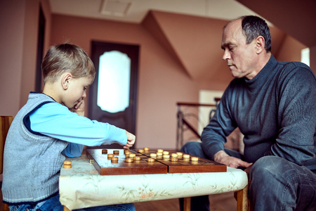 parlour games: Caucasian grandfather and grandson playing checkers