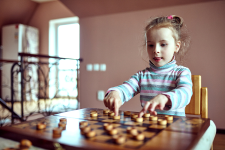 parlour games: Little funny girl playing checkers .