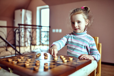 Little funny girl playing checkers .