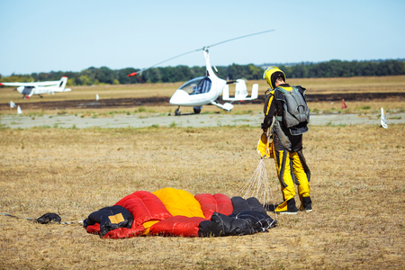 caida libre: Skydiver with red parachute after landing on the ground.
