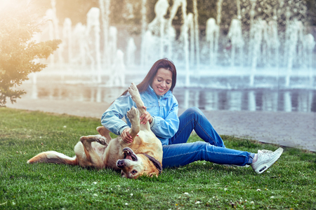 Woman playing with her big dog outdoors in park