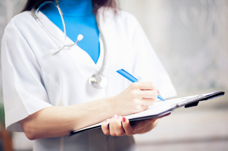 Close-up Of famale Doctor Filling The Medical Form