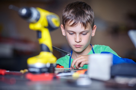 concentrate: teenager in professional training using fret saw Stock Photo