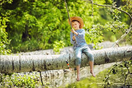 Een jongen op de oever van het kanaal, vissen