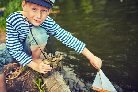 A young boy dreams of becoming a sailor Stock Photo