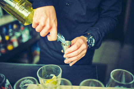Young bartender pouring cocktail drink into glass