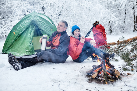 Happy couple  over a campfire in winter snowy forest