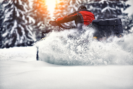 Rider driving in the quadbike race in winter in the forest