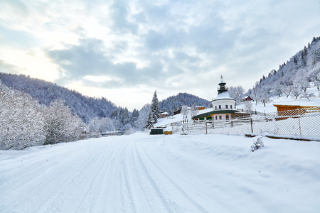 Beautiful winter rural scenery in the mountainous village outskirts at sunrise Stock Photo