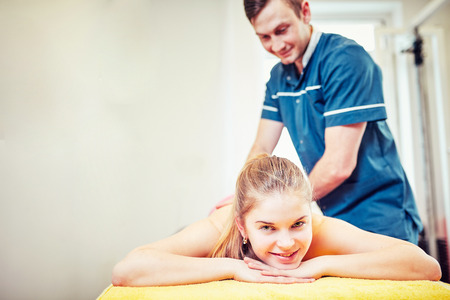 A young professional male masseur makes Thai massage. Stock Photo