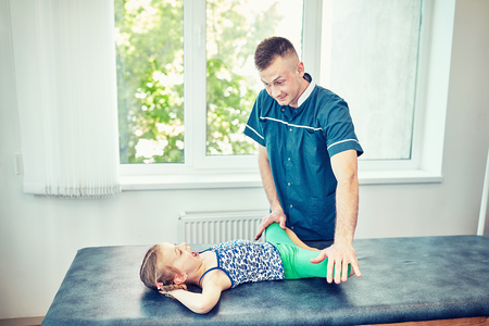 The doctor is carrying out a course of rehabilitation with a girl. Standard-Bild