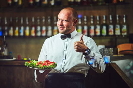Waiter showing hospitality and serving visitors in bar