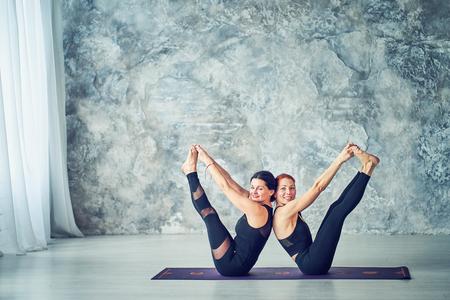 Junge Frau, die Pose hält, Yoga im Studio praktiziert Standard-Bild