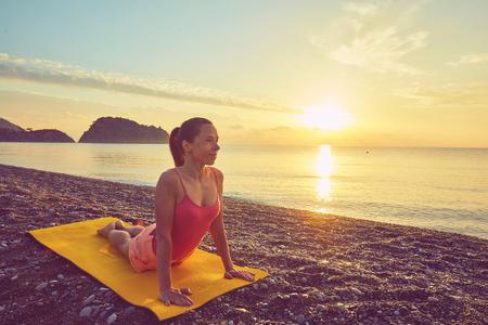 yoga at sunset on beach. woman doing yoga
