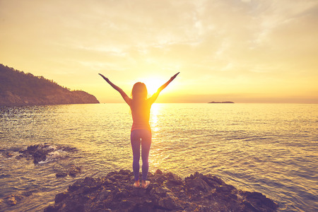 Yoga bei Sonnenuntergang am Strand. Frau macht Yoga