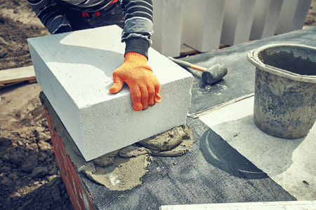Builder lays aerated concrete block at a construction site