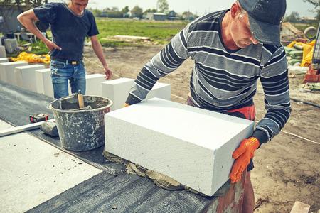 Baumeister legt Porenbetonblock auf einer Baustelle Standard-Bild