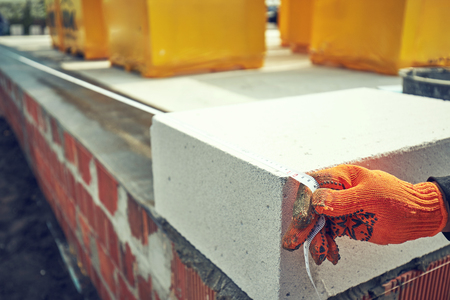 Builder lays aerated concrete block at a construction site 스톡 콘텐츠 - 122263017