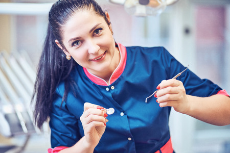 Portrait of female dentist. She standing at her office and she has beautiful smile. 스톡 콘텐츠 - 125386552