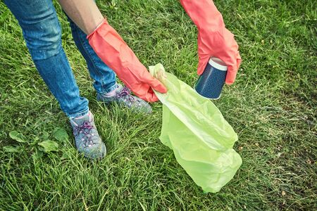 Ecology protection concept. Woman volunteer collecting garbage in park