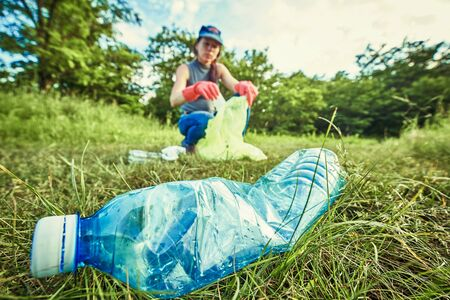 Ecology protection concept. Woman volunteer collecting garbage in park 스톡 콘텐츠 - 125388065