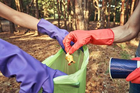 Ecology protection concept. Woman volunteer collecting garbage in park 스톡 콘텐츠 - 125388428