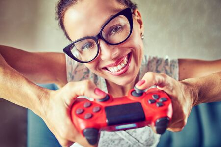 Young woman emotionally making faces playing video games