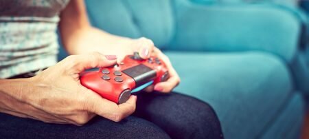 Hands using video game controller, on the couch at home