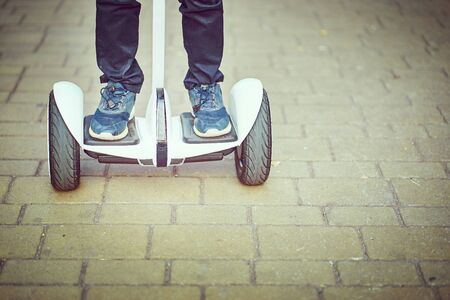 Teenager rides whirl on a hoverboard over park paths