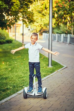 Child on hover board. Kids riding scooter Stok Fotoğraf