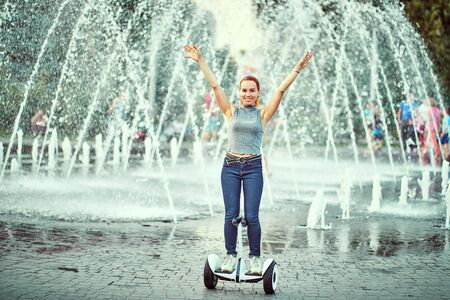 girl rides whirl on a hoverboard over park paths