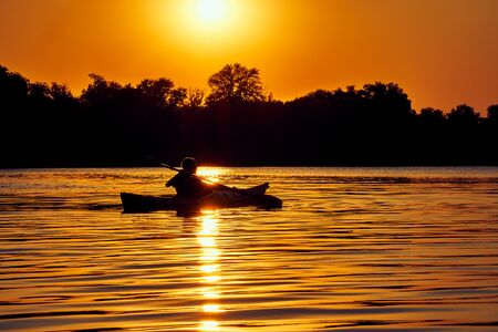 Kayaking couple ride along the river at sunset Stok Fotoğraf